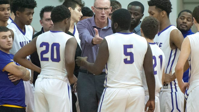 Male head basketball coach Willie Feldhaus talks to his players during a time-out.Jan. 19, 2018