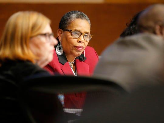 School board president Carolyn Jones listens during