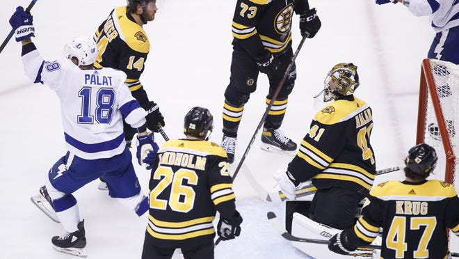 Tampa Bay Lightning left wing Ondrej Palat (18) celebrates a goal as Bruins goaltender Jaroslav Halak and teammates look on during Saturday's Stanley Cup playoff game in Toronto. The Lightning won, 3-1, to take a 3 games to 1 series lead.