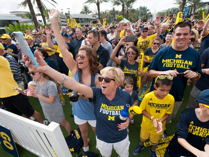 Hundreds of fans cheer along with the Michigan Marching