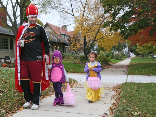 Connor Broderick of Milwaukee, dressed as King James, takes his twin 3-year-old daughters, Kalia (center) and Malani, to trick-or-treat in Shorewood.