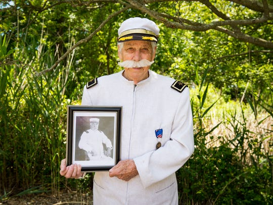 Thomas Creekmore holds a photo of Admiral Dewey on