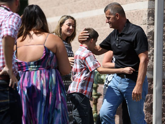 Mount Olive Police Chief Mark Spitzer hugs his family as he takes his ceremonial walk-out Friday,  retiring after 33 years. July 29, 2016, Mt. Olive, NJ