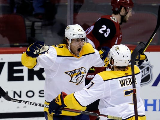 Nashville Predators right wing Craig Smith (15) celebrates with Yannick Weber (7) after scoring during the third period of the team's NHL hockey game against the Nashville Predators, Thursday, Jan. 4, 2018, in Glendale, Ariz. The Coyotes defeated the Predators 3-2. (AP Photo/Rick Scuteri)