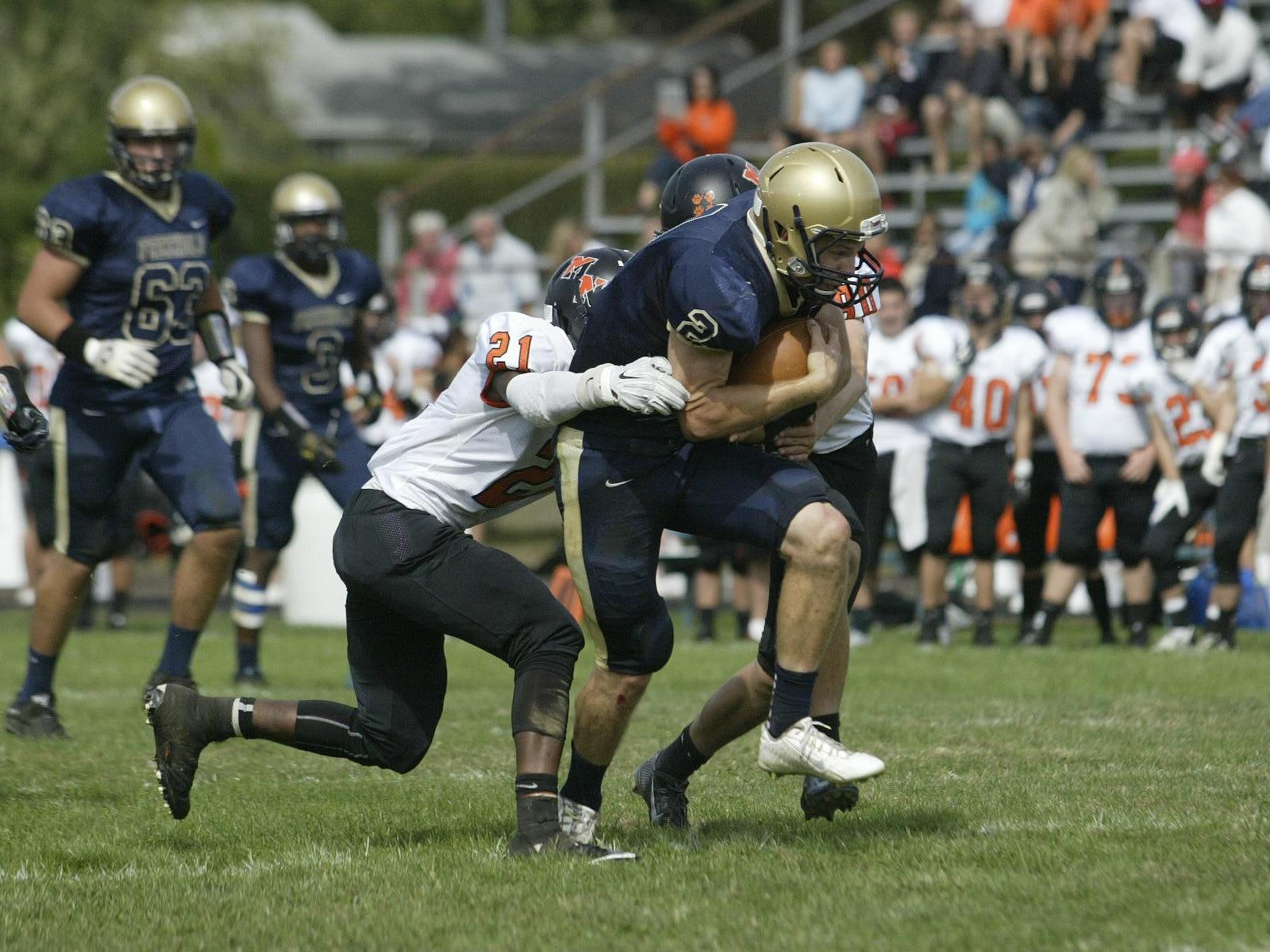 Freehold High School quarterback Jake Curry runs through two Middletown North defenders enroute to a big gain in the second quarter during a Shore Conference game Saturday afternoon, at Freehold.