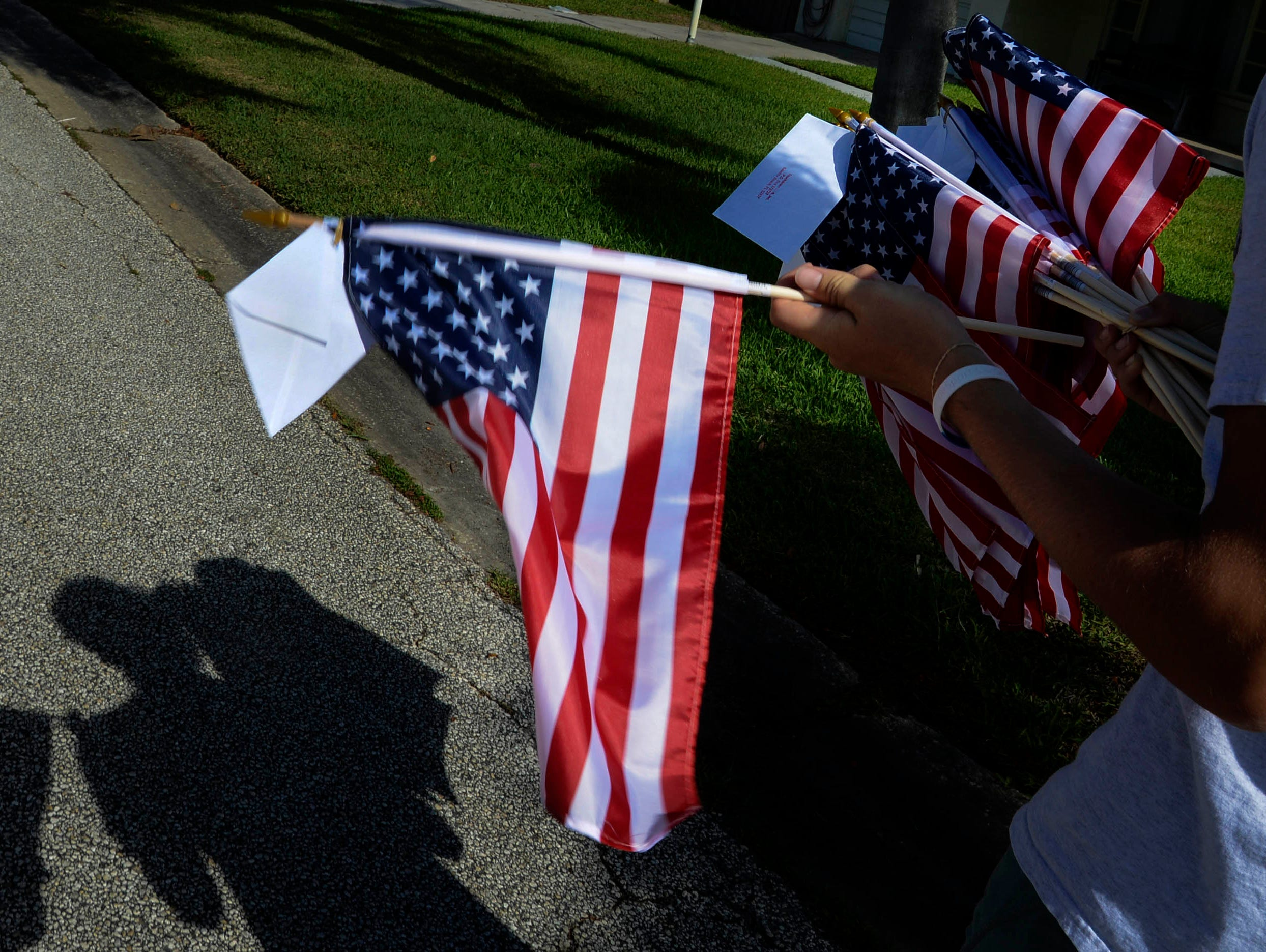 Students from Satellite High's football and ROTC squads help distribute American flags to town residents Thursday morning. The flags are part of a fundraiser for the school.