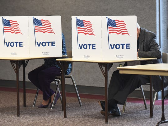 Voters fill out ballots at William M. Costick Activities Center in Farmington Hills.