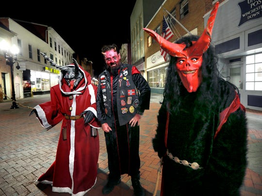 People dressed as Krampus roam the Loudoun Street Mall in Winchester, Va., on Dec. 10. A folklore creature, the Krampus is a half demon, half goat that appears during the Christmas season in search of children that have been naughty. (Ginger Perry/The Winchester Star via AP)
