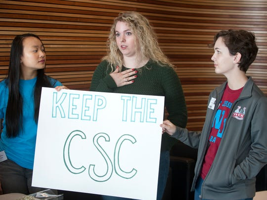 llison Tu, left, aand Evelyn Madill, right, listen to junior Laura Duke speak about what the CSC means to her.