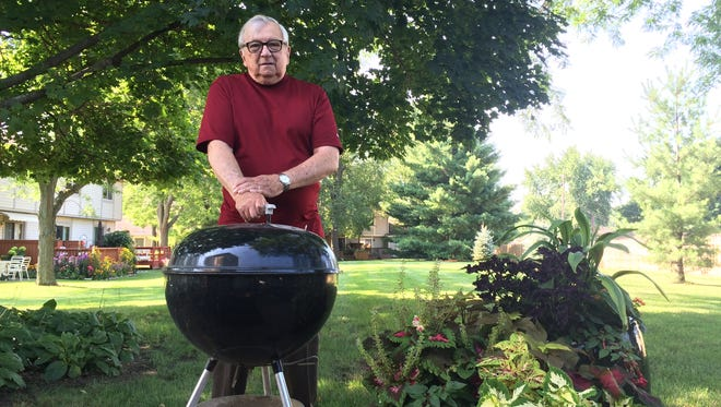 Bruce Cornelius, with his Weber grill at his home on Aug. 17, 2016,  is fighting for the right to grill with charcoal at his Haslett condominium.