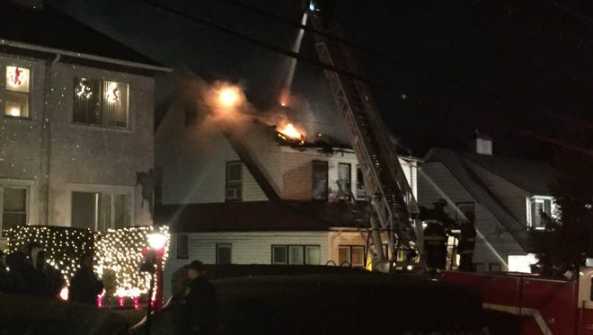 Firefighters battle flames after they burst through the roof at 37 N. Columbus Ave. in Mount Vernon, Dec. 14, 2016.