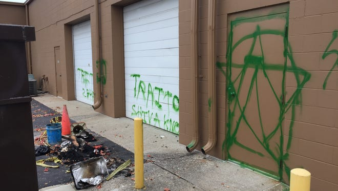 Hateful graffiti and remains of an attempt arson sit behind a northwest side business owned by the Patnaik family.