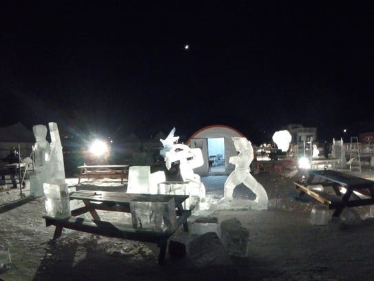 John Merruci (from Marshall, Mich.) and Martin Folk (from Pinckney, Mich) ice sculptures at night.