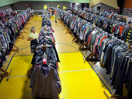 It's children's consignment sale time. Volunteer Elaine Burchett hangs clothes among numerous racks stretching nearly the length of the gym floor Sunday, July 13, 2014, at Friendship Christian School in Lebanon. Burchett has been involved with the Friendship consignment sale for 10 years.