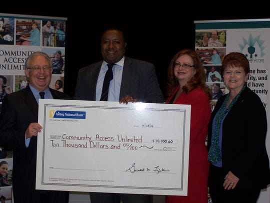 Sid Blanchard (left), executive director of CAU, accepts a $10,000 grant from Valley National Bank from bank representatives (left to right) Mwaura Muroki, Mary Ann Betz and Ellen Scardena.