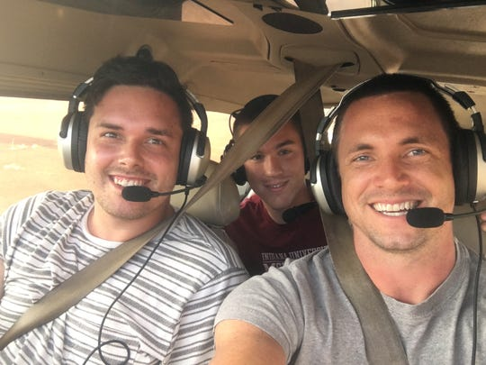 Jacob Cott (middle) flies on an airplane with his friend