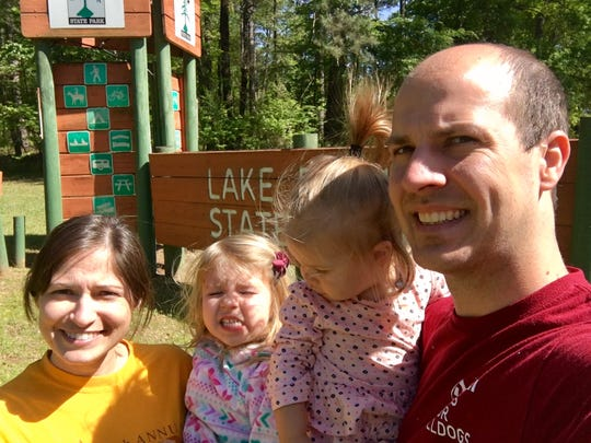 "Travel and tourism reporter Leigh Guidry and family are visiting all 21 Louisiana state parks and taking a ""state park selfie"" in front of each park's sign. Here they squint in front of the entrance to Lake Bistineau State Park."