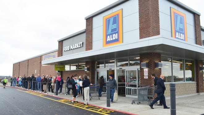 Shoppers file into the new Aldi, 2750 Heartland Drive in Coralville, Iowa, during the grocery store's grand opening Thursday morning, Nov. 12, 2015.
