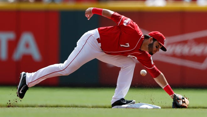 The ball gets past Cincinnati Reds shortstop Eugenio Suarez on a throwing error during the first inning of a baseball game against the St. Louis Cardinals, Sunday, Sept. 13, 2015, in Cincinnati.