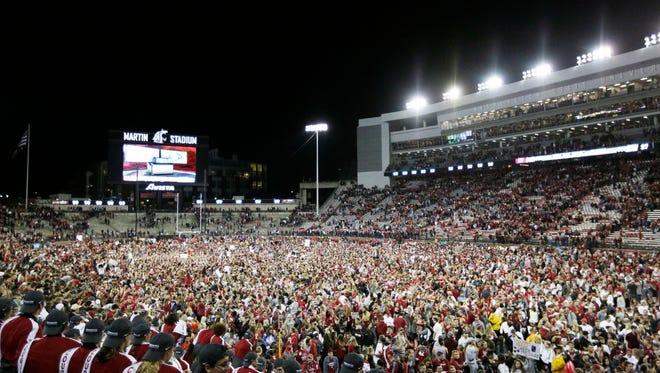 Fans and players celebrate Washington State's 30-27 win over Southern California, and it will cost the school $25,000.