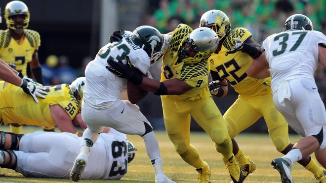 Sep 6, 2014; Eugene, OR, USA; Michigan State Spartans running back Jeremy Langford (33) is tackled by Oregon Ducks defensive lineman Arik Armstead (9) at Autzen Stadium. Mandatory Credit: Scott Olmos-USA TODAY Sports