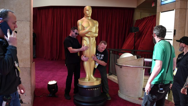 Workers set up an Oscars statue as preparations are made ahead of the 91st Annual Academy Awards at the Dolby Theatre in Hollywood, California on February 24, 2019.