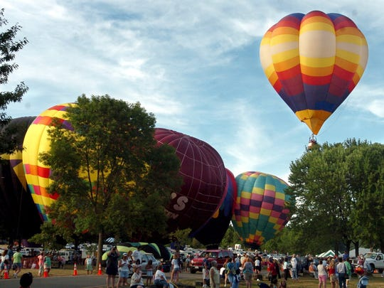 A hot air balloon goes up ahead of the pack during