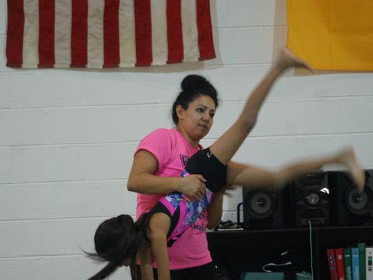 Irma Chacon assists a student with a handstand during a Wednesday night Dust Devils gymnastics class.
