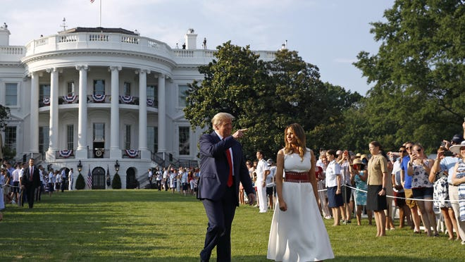 """President Donald Trump and first lady Melania Trump walk on the South Lawn of the White House during a """"Salute to America"""" event, Saturday, July 4, 2020, in Washington."""