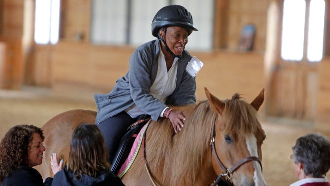 The Therapeutic Equestrian Center in Cold Spring has teamed up with Cortlandt's Hudson Valley Hospital Center for a pilot program, which will pair women with breast cancer with equine partners as a way to aid in their recovery. Vanessa Edwards of Salisbury Mills, who recently had a mastectomy and is undergoing chemotherapy, smiles after her riding lesson with Hoss, May 8, 2014 at Therapeutic Equestrian Center in Cold Spring.