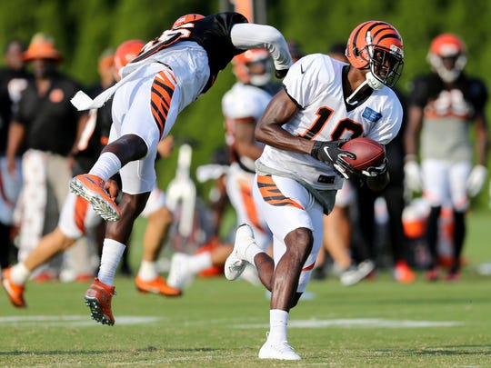 Cincinnati Bengals wide receiver A.J. Green (18) makes a catch as Cincinnati Bengals defensive back Shawn Williams (36) avoids hitting him during Cincinnati Bengals training camp practice, Friday, Aug. 3, 2018, on the practice fields next to Paul Brown Stadium in Cincinnati.