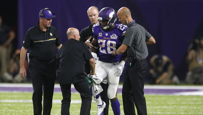 Minnesota Vikings running back Adrian Peterson (28) is helped off the field Sept. 18 after getting injured during the second half against the Green Bay Packers in Minneapolis.