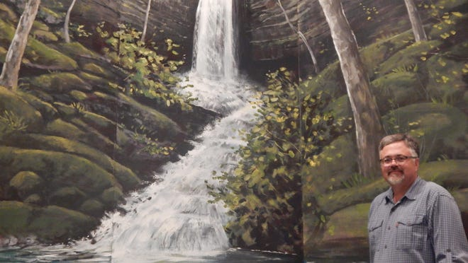 Local artist Duane Hada is shown with the baptismal mural he recently completed at Twin Lakes Baptist Church. The mural of the Upper Eden Falls in Lost Valley State Park near Ponca adorns the church's baptismal area.