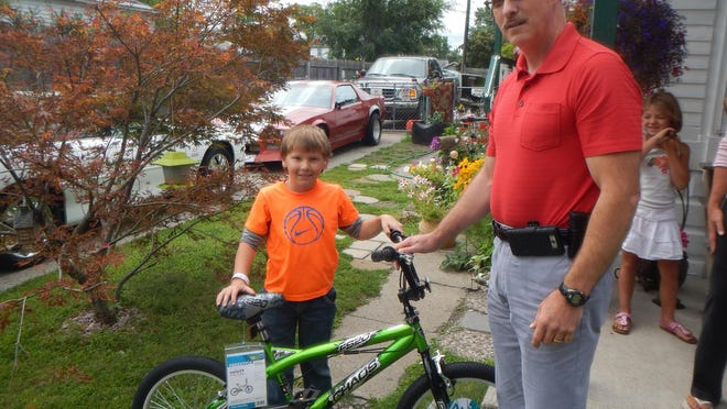 Quinton Morgan accepts a new bicycle from Port Huron police Detective Keith Merritt on Tuesday, Aug. 11, 2015. Police pooled resources to buy Quinton a new bicycle after his was taken in June.