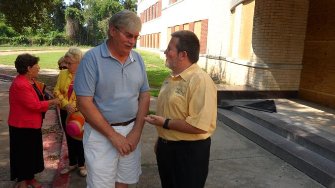 Rich Dupree (right), chief of staff for Pineville Mayor Clarence Fields, and preservationist Paul Smith (left foreground) talk Monday after touring the closed Huey P. Long Medical Center building in Pineville. In the background are Ina LaBorde (red jacket) and Helen Moore (yellow jacket).
