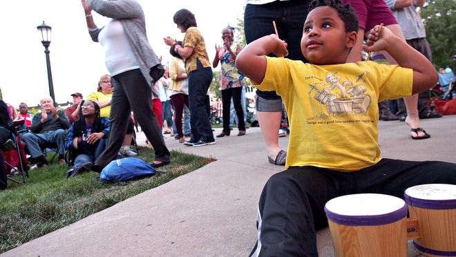 Maddox Schwalm-Bell, 4, of Iowa City jams on a tiny drum while watching a percussionist on stage on Sept. 19, 2014, during the Iowa Soul Festival.