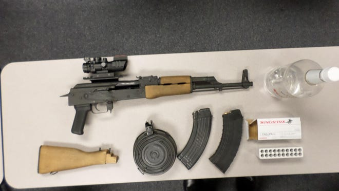 This AK-47 semiautomatic rifle, plus ammunition magazines, an ammunition box and vodka, were taken from two men Friday near the parking deck in downtown Plymouth. The pair face misdemeanor charges.