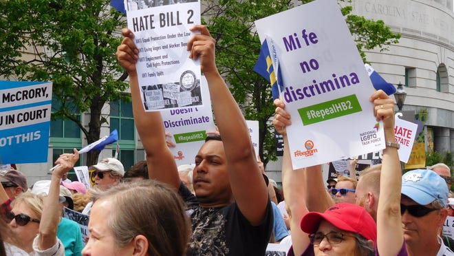 Anti-HB2 protesters hold signs up at a rally in Raleigh earlier this year. U.S. District Judge Thomas Schroeder scheduled oral arguments for Monday on whether the state can require transgender people to use restrooms in many public buildings that match their birth certificates, rather than their gender identities.