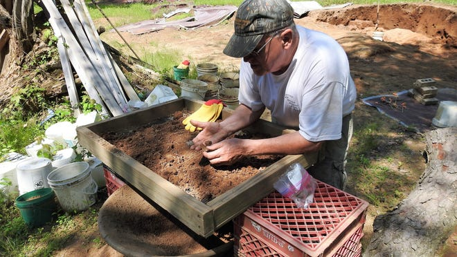 Mark Hersman sifts through dirt looking for artifacts from prehistoric people at a site in eastern Coshocton County. The 1-acre site was home to a Native American village that spanned generations. He routinely finds arrowheads, flint and pieces of pottery.