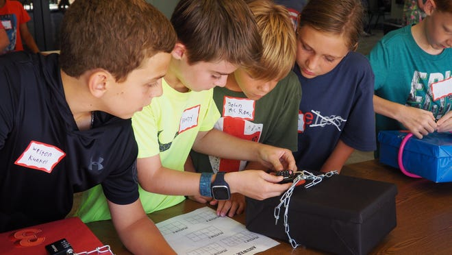 Tweens try the lock to see if their team successfully answered a question to solve a puzzle as part of the library's Tween Escape Room.