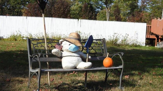 This mask-wearing teddy has been seated on the bench across from the Gardner Municipal Golf Course for many months waving at the children. He is ready to rake up all the falling leaves.