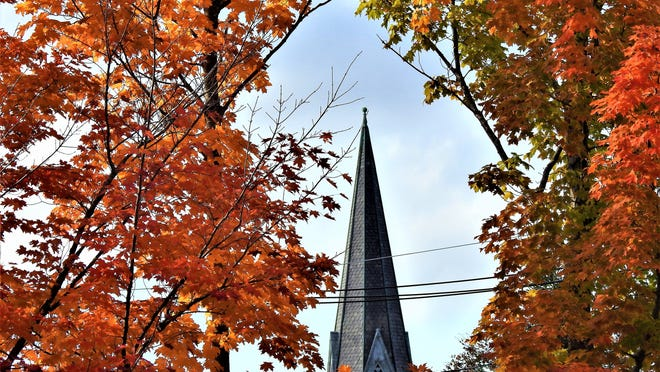 Winchendon's Unitarian Universalist Church steeple is seen through the trees.