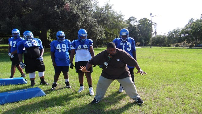 Savannah High football coach Michael Moore works with his offensive line at a recent practice.