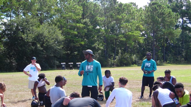Islands football coach DeShawn Printup talks to his team after a practice this season.