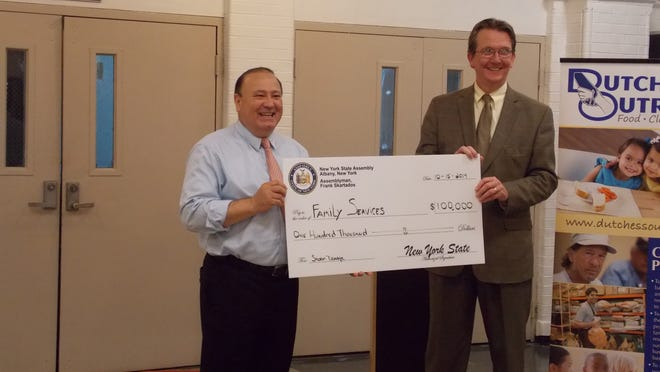 Assemblyman Frank Skartados presents Family Services CEO Brian Doyle with a $100,000 grant for repairs at the Family Partnership Center in Poughkeepsie.