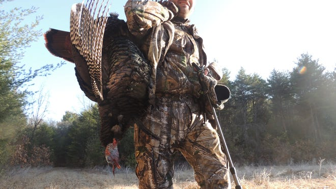 Charles Fischbach carries his turkey out of the field Saturday morning.