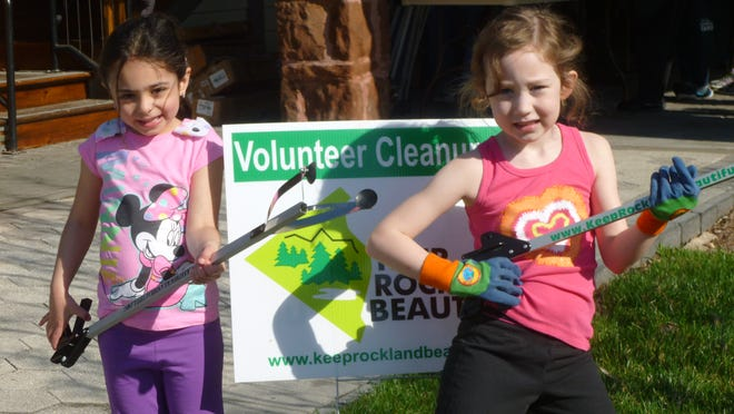 """Two young volunteers pose with litter grabbers as they help Keep Rockland Beautiful. """"It's hard to feel that just one person can make a difference,"""" said one Nanuet cleanup volunteer, teenager Caitlin Knauss. """"The cleanup gives me a sense of connection to this community, and the cause is something I really believe in."""""""