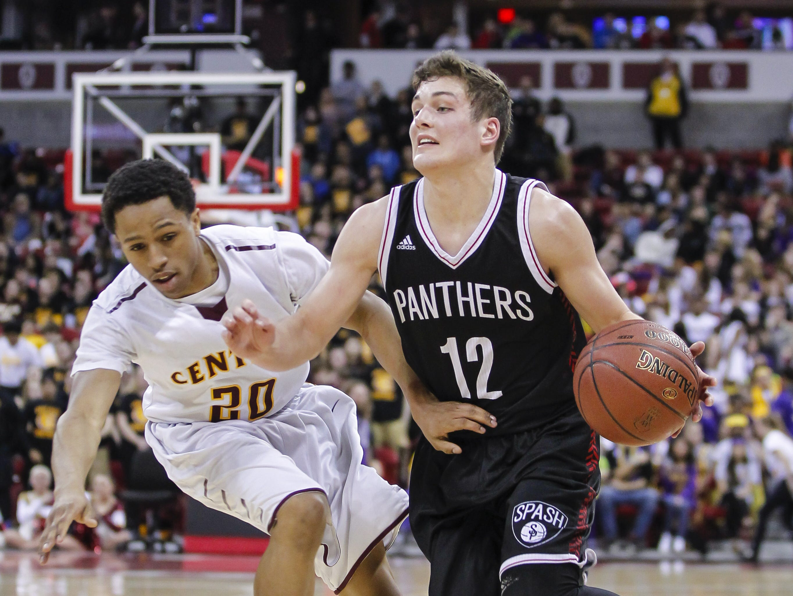 Stevens Point's Trev Anderson (12) drives past West Allis Central's Geo Owens during the second half of their Division 1 semifinals in the WIAA boys state basketball championships on March 20 in Madison.