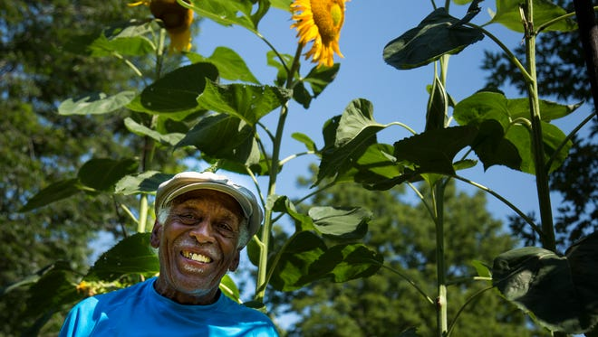 Marvin Porter poses for a portrait in front of his sunflower garden. He grew his tallest flower this year at 14-feet.