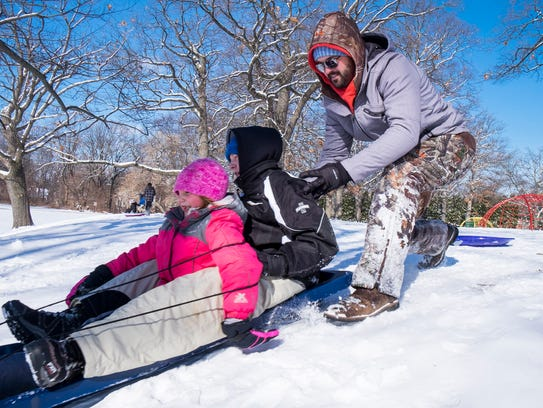 Brad Kegebein, of Croswell, right, pushes his kids